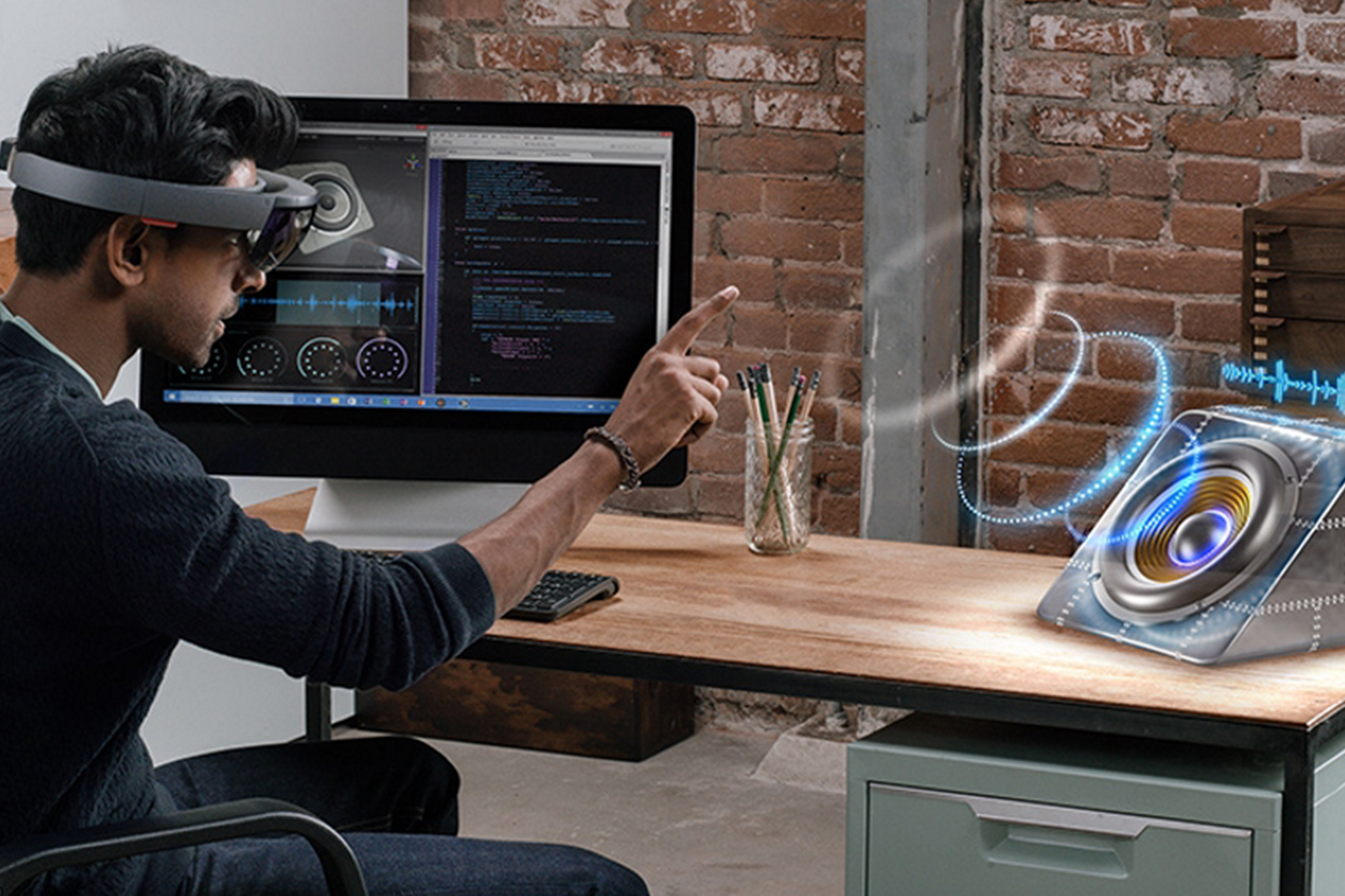 Microsoft 'MR' HoloLens - Man using headset at desk with speaker.
