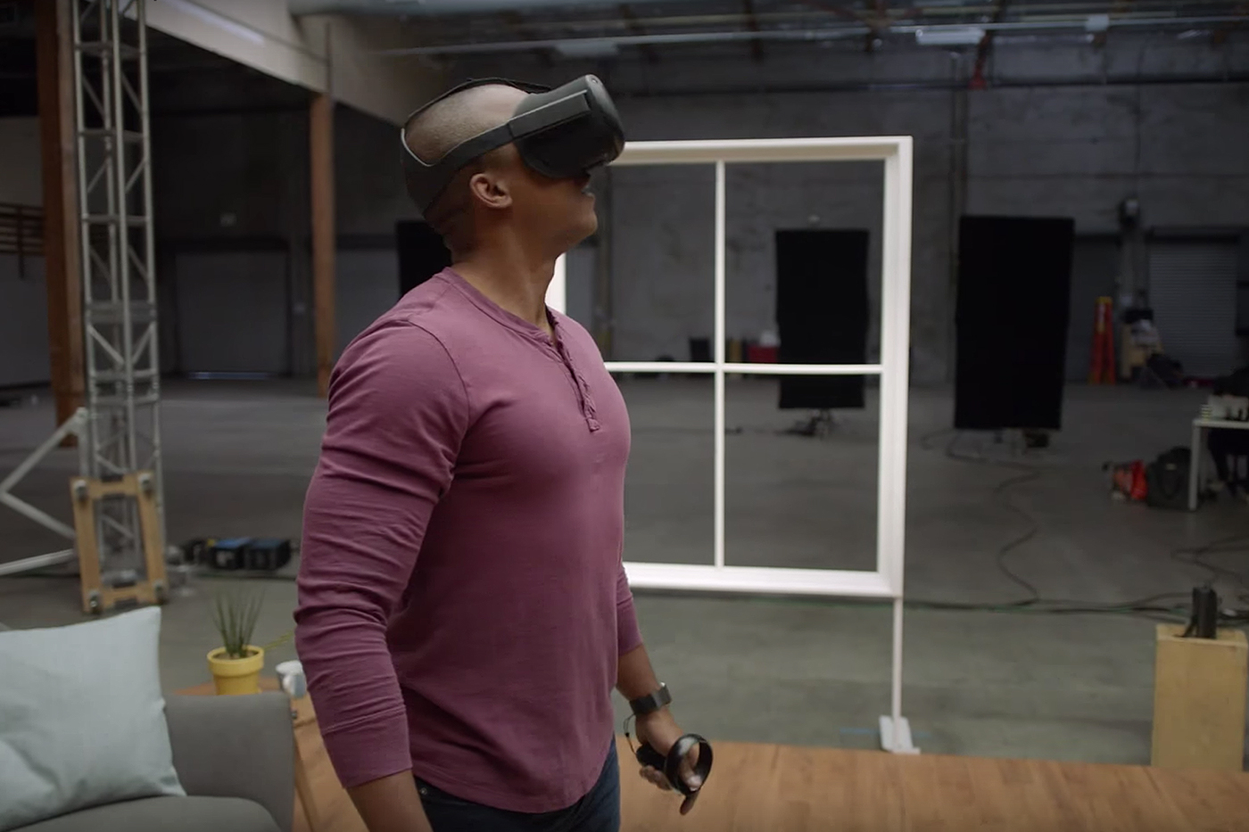 A man wearing the Oculus Santa Cruz Headset in a room.